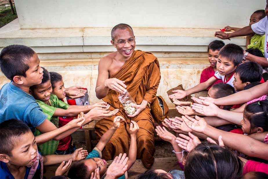 man-in-monk-dress-between-group-of-children